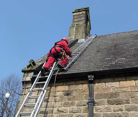 Ascending the ladders with the rope attached to a harness as a safety device